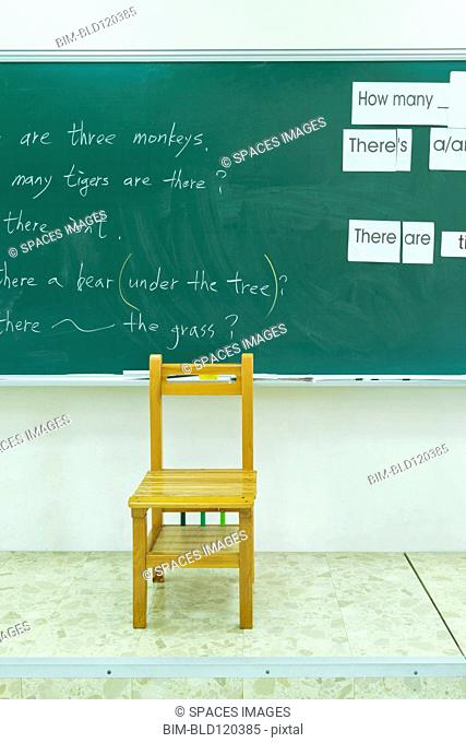 Empty chair at blackboard in classroom