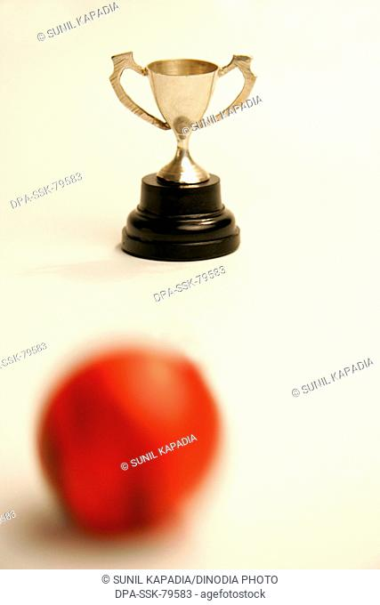 Small metal cup with red and black rubber ball of soccer or football sport