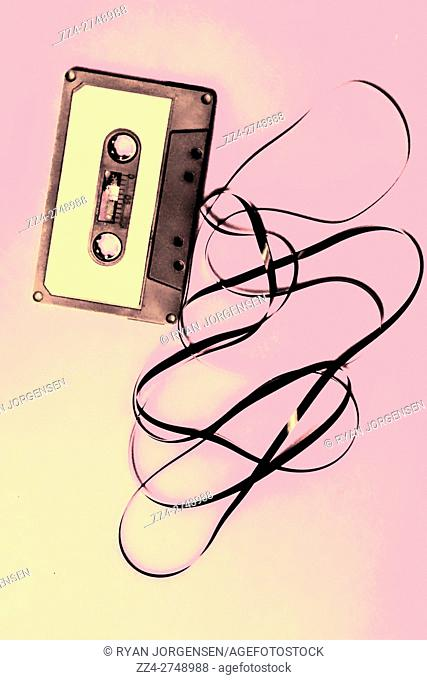 isolated audio cassette with black tape on pink backdrop