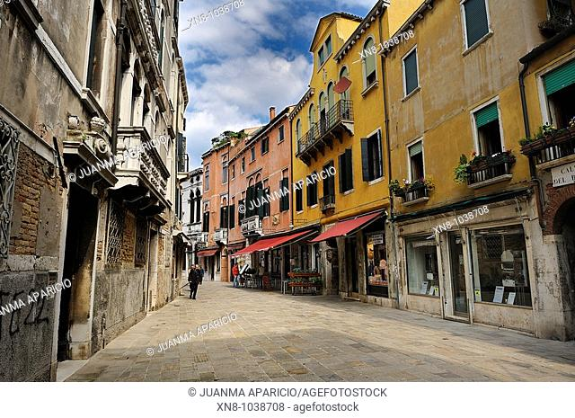 Street in the city of Venice with colored facades and shops with red awnings