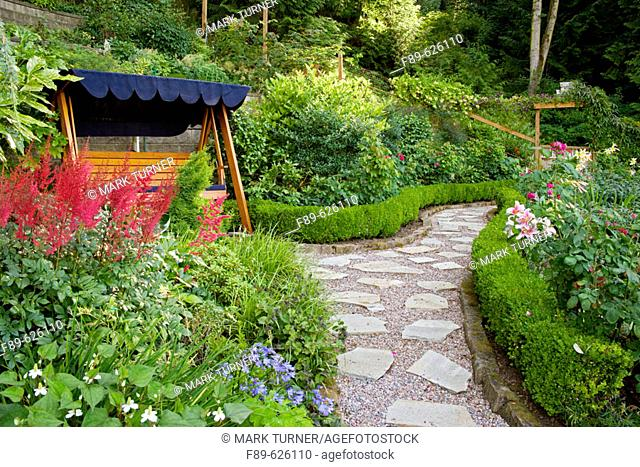 Covered wooden swing beside Red Astilbe w/ stepping stone path bordered by dwarf Boxwood hedges (Astilbe cv.; Buxus sempervirens)