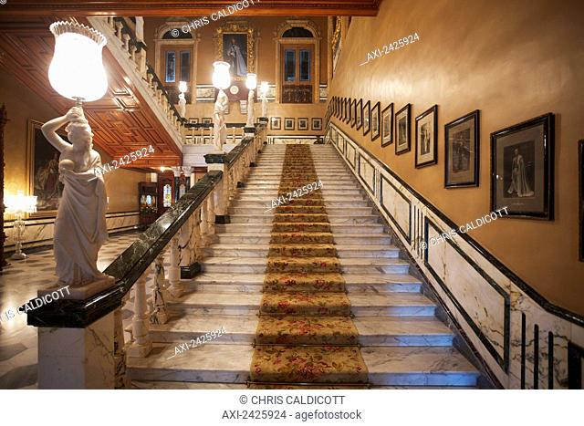 Staircase with photographs lining the wall and statues on the railing in Falaknuma Palace; Hyderabad, Andhra Pradesh, India