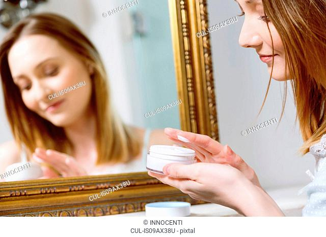 Woman holding face cream looking down smiling