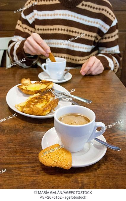 Coffee with croissant and biscuits and man having breakfast in a cafeteria