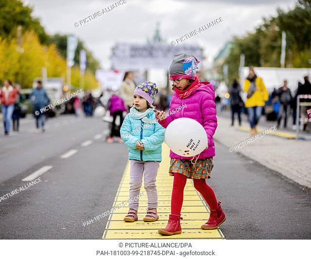 03 October 2018, Berlin: Four-year-old Pauline (l) and six-year-old Florentina run in front of the Brandenburg Gate at the Bürgerfest on German Unification Day