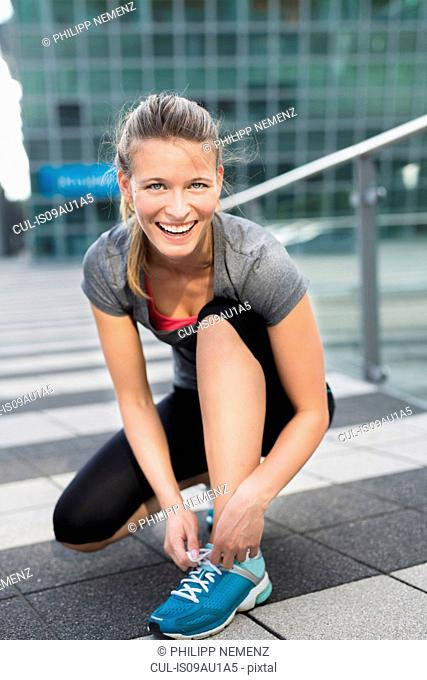 Portrait of young female runner tying trainer laces in city