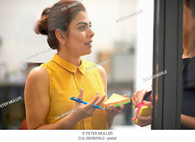 Two businesswomen behind office glass wall having discussion