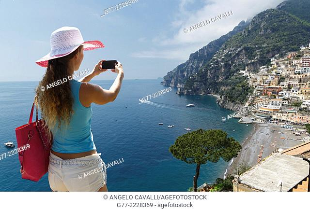 Woman taking pictures of Positano, on the Amalfi Coast, Italy