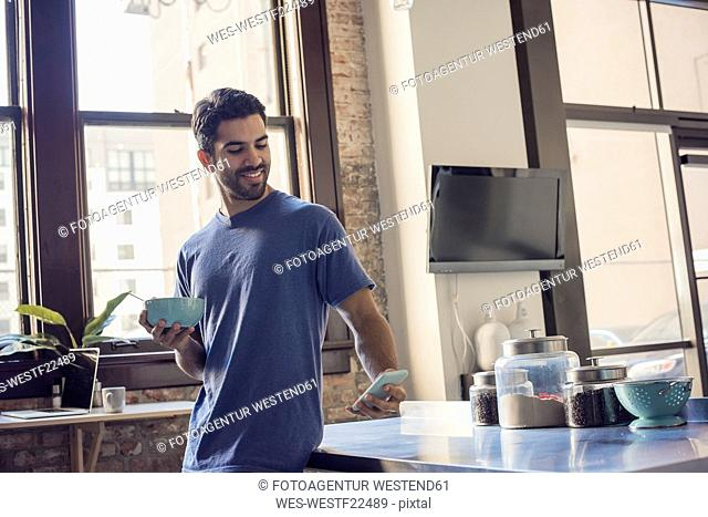 Young man standing in kitchen using smart phone