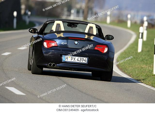 BMW Z4 3.0 si Roadster, model year 2006-, black, driving, diagonal from the back, rear view, country road, open top