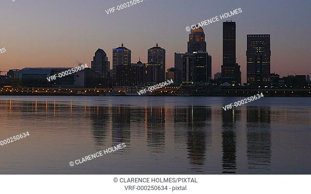 The illuminated skyline of Louisville, Kentucky is reflected in the waters of the Ohio River as the sky lightens during morning twilight