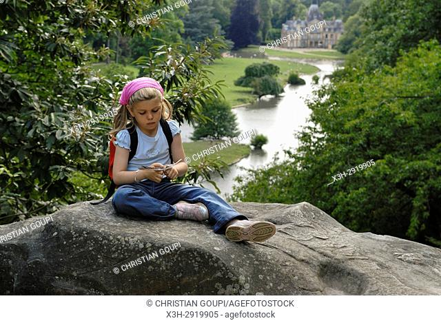 7 years old little girl in the Park of the Chateau de Sauvage, Emance, Yvelines department, Ile-de-France region, France, Europe