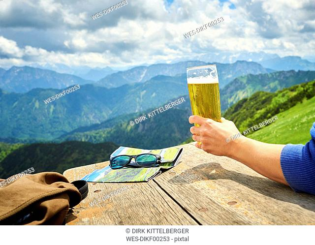 Germany, Chiemgau, hand of hiker on Hochfelln Mountain holding glass of beer, partial view
