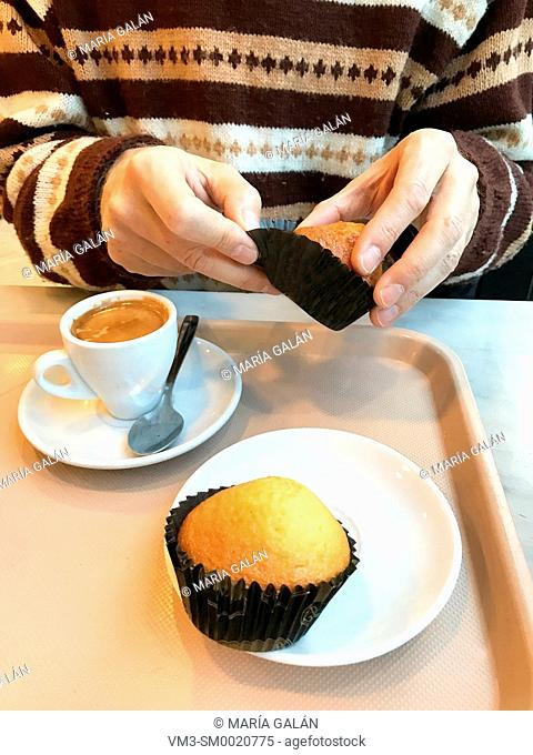 Man hand's having sponge cakes with a cup of coffee in a cafeteria