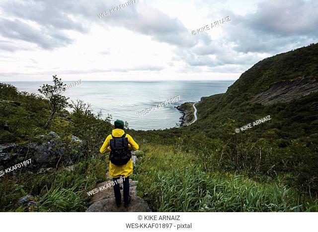 Norway, Lofoten, rear view of man standing on coastal path