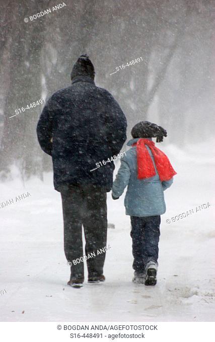 Bucharest, Ferentari neighborhood, Romania, Europe, EU - Father and son walking through blizzard