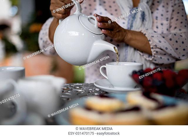Mid section of woman pouring tea in cup