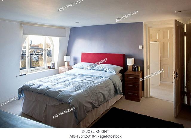 Double bed with red headboard in modern bedroom, London