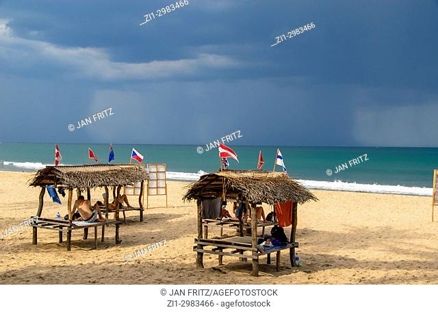small benches with grass roofs for tourists at the beach and rain clouds at sea at Trincomalee, Sri Lanka