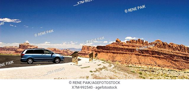 Mini van stopped at viewing area overlooking Spotted Wolf Canyon / San Rafael Reef in the San Rafael Swell in the American Southwest