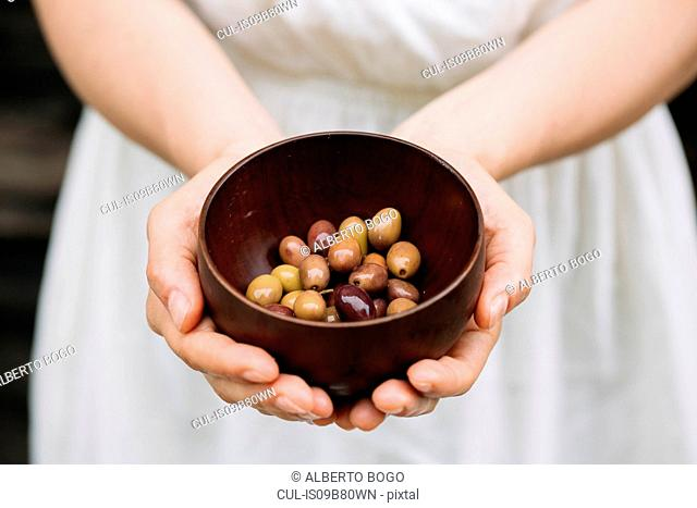 Woman holding bowl of olives, mid section