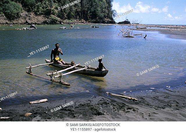 Melanesian man and his children in a traditional dugout canoe in the estuary at Sulphur Bay, Tanna, Vanuatu