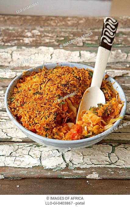 Traditional African cooking. Baked cabbage with bacon and potato. Ingredients - cabbage, potatoes, onions, tomatoes, grated cheese and crumbs