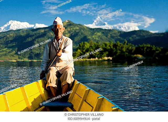 Nepalese man rowing traditional boat