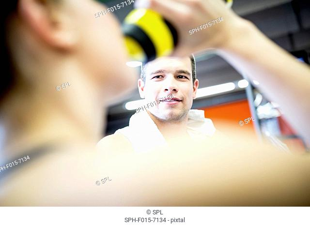 MODEL RELEASED. Man looking at woman while drinking water in gym