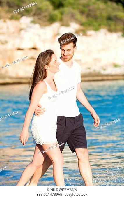 junges verliebtes paar spaziert am strand im sommer urlaub