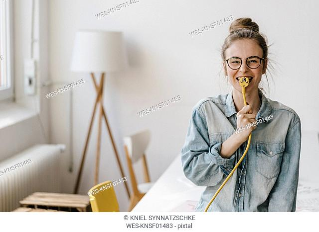 Portrait of happy young woman with power cable
