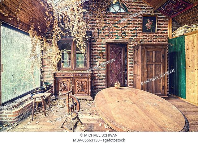 Conservatory in an abandoned farm with table and spinning wheel