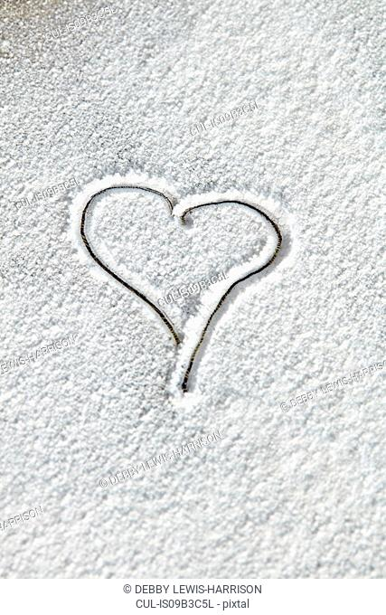 Overhead view of heart shape drawn in white icing sugar
