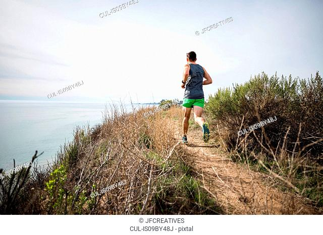 Runner jogging on cliff top, Santa Barbara, California, USA