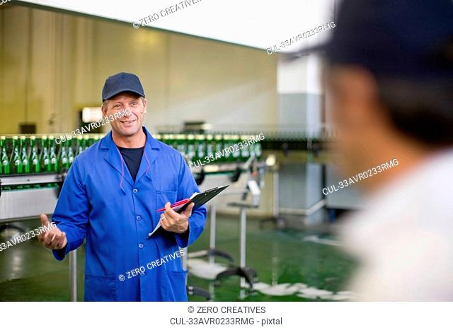 Worker with clipboard in factory