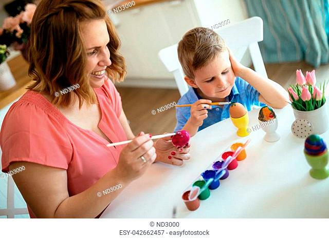 Mother with kid making easter decoration and painting eggs