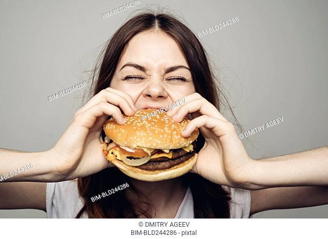 Caucasian woman eating cheeseburger