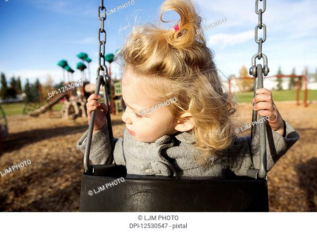 A cute young girl looking away while swinging in a playground during the fall season; Spruce Grove, Alberta, Canada