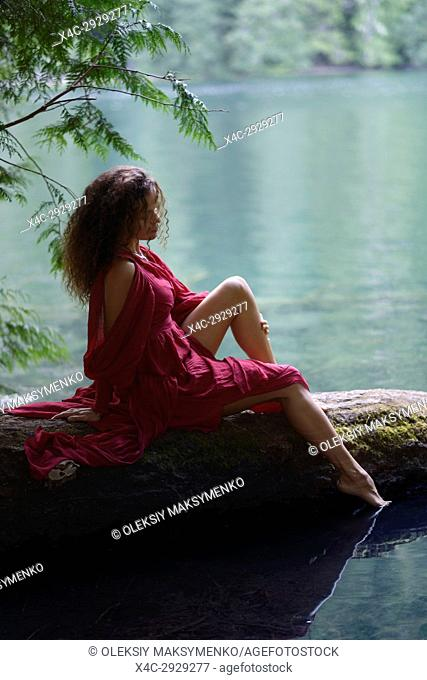 Tranquil romantic portrait on a beautiful young woman sitting on a tree trunk in summer nature scenery with thoughtful expression dipping her foot in calm blue...