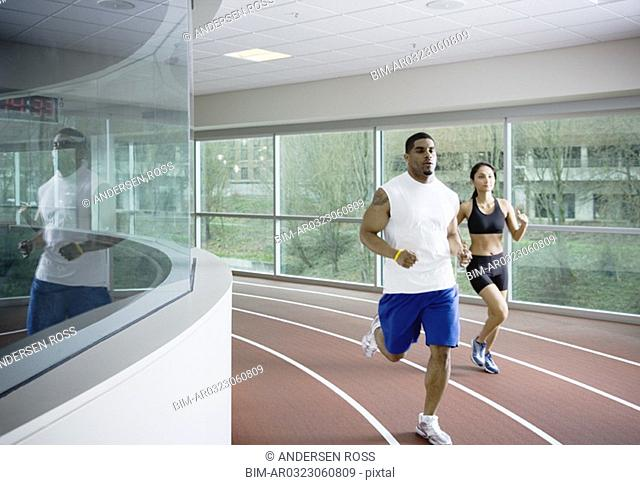 Man and woman running on indoor track