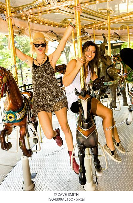 Two young women riding horse carousel in park
