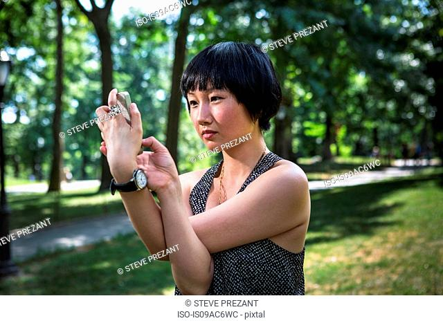Young woman holding smartphone with arms twisted