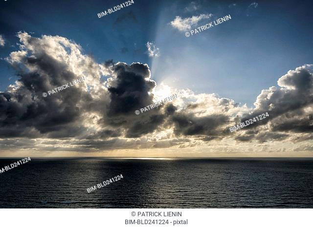 Sunbeams behind clouds over ocean