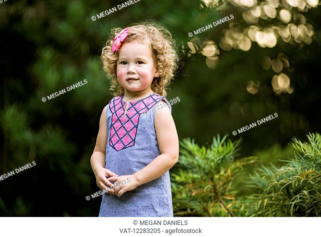 A three-year-old girl with curly hair at JC Raulston Arboretum; Raleigh, North Carolina, USA