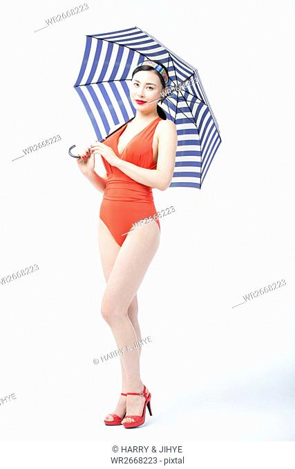 Young smiling woman wearing swimsuit and parasol posing