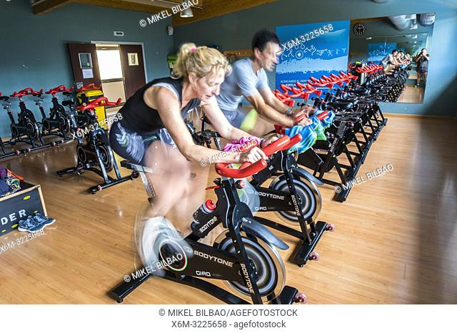 Woman and men in a spinning session