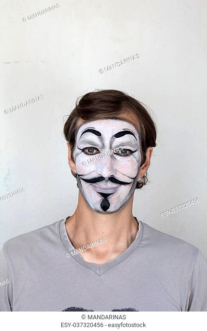 Smiling man with V mask face painting