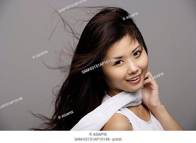 Chinese woman wearing white, hair blowing