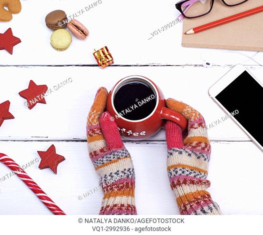 two hands in knitted mittens hold a red cup with hot black coffee on a white wooden table, top view