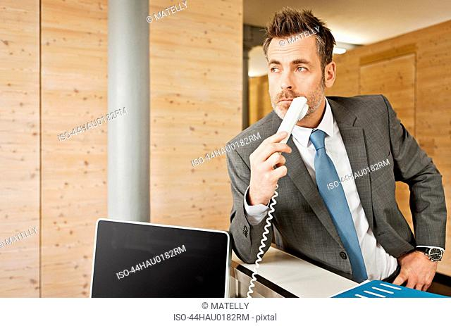 Businessman holding phone in office